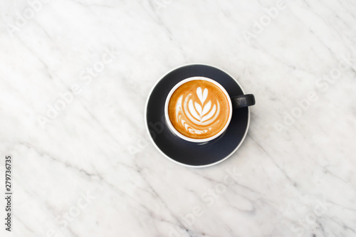 Photo sur Toile Cafe Dark gray cup of fresh cappuccino with classic latte art on white marble table trendy background. Empty place for text, copy space. Coffee addiction concept. Top view.