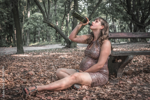Fotografie, Tablou  Pregnant woman drinking wine in the park - alcoholism concept