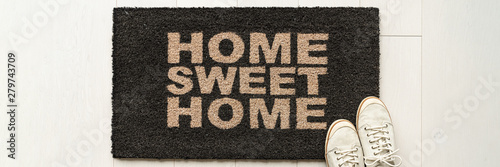 Photo Home condo door mat sweet home doormat text at condo entrance with casual shoes panoramic banner