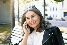 Happy To Hear You. Smiling Positive Elderly Woman Wearing Stylish Leather Jacket And Sunglasses On Her Head Enjoying Nice Phone Conversation, Speaking To Old Good Friend, Sitting On Bench Outside