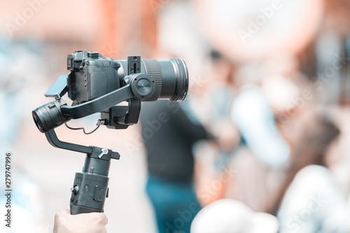 Fototapeta Video shooting with a camera with a tripod with a black stabilizer obraz na płótnie
