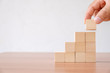canvas print picture - Business concept of ladder career path and growth success process. Hands of men arranging wood cube block stacking for top staircase shape on wooden table.