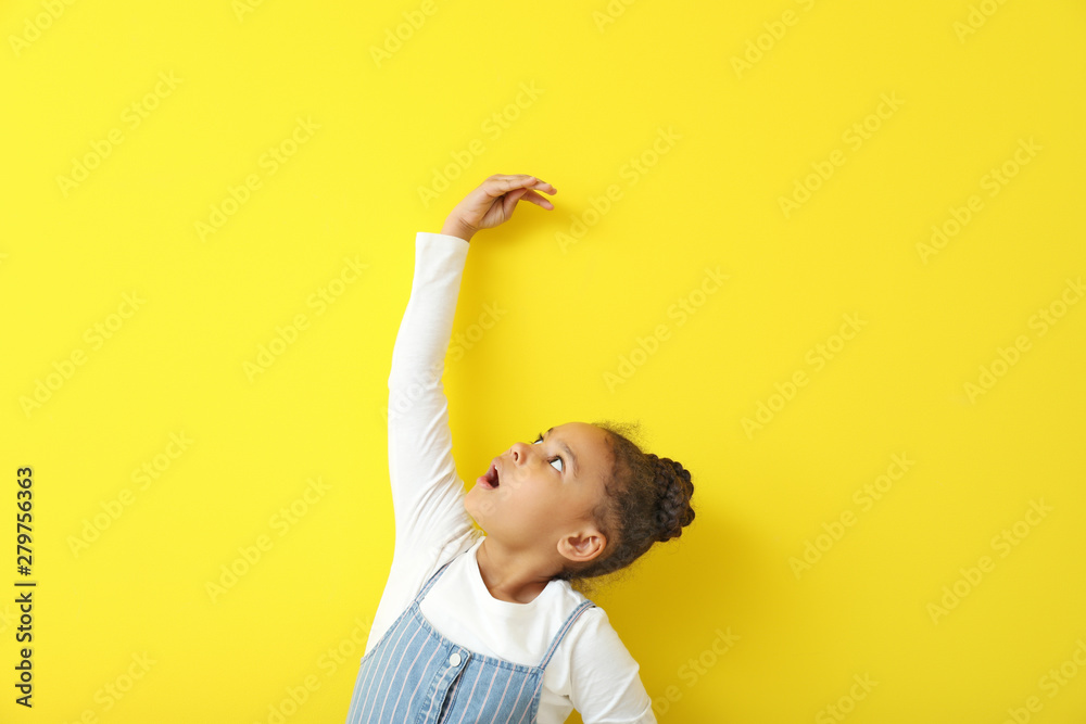 Fototapety, obrazy: Cute little African-American girl measuring height near color wall