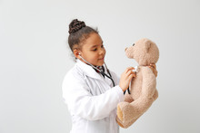 Portrait Of Little African-American Doctor On White Background