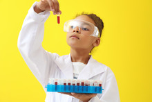 Little African-American Laboratory Assistant Holding Test Tubes With Blood Samples On Color Background