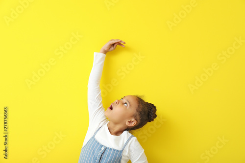 Pinturas sobre lienzo  Cute little African-American girl measuring height near color wall