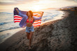 Happy woman running on beach while celebrateing independence day and enjoying freedom in USA