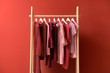canvas print picture - Rack with hanging clothes on color background