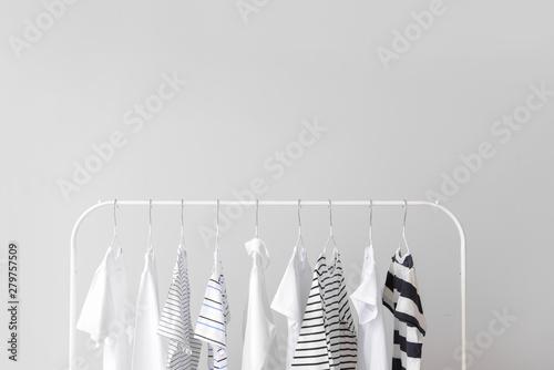 Fotografía  Stylish kid clothes hanging on rack against light background