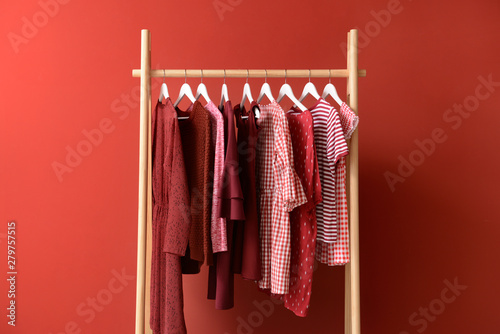 Obraz Rack with hanging clothes on color background - fototapety do salonu