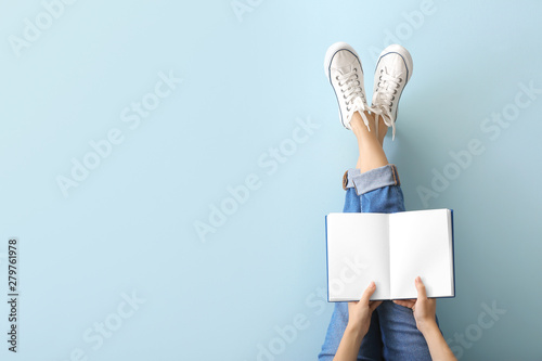 Fotografiet Woman with book on color background
