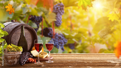 Leinwand Poster Vines with grapes and old cask on vintage wooden table, still-life