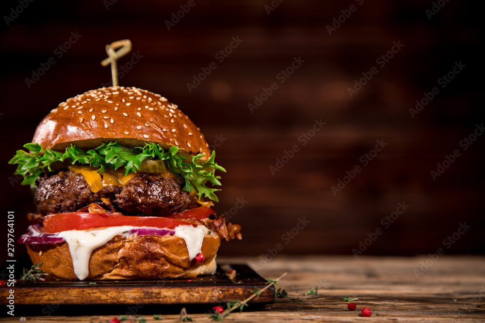 Fototapety, obrazy: Close-up of home made tasty burger on wooden table.