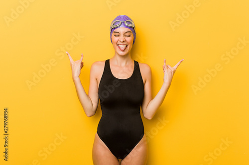 Young swimmer caucasian woman showing rock gesture with fingers - 279768934