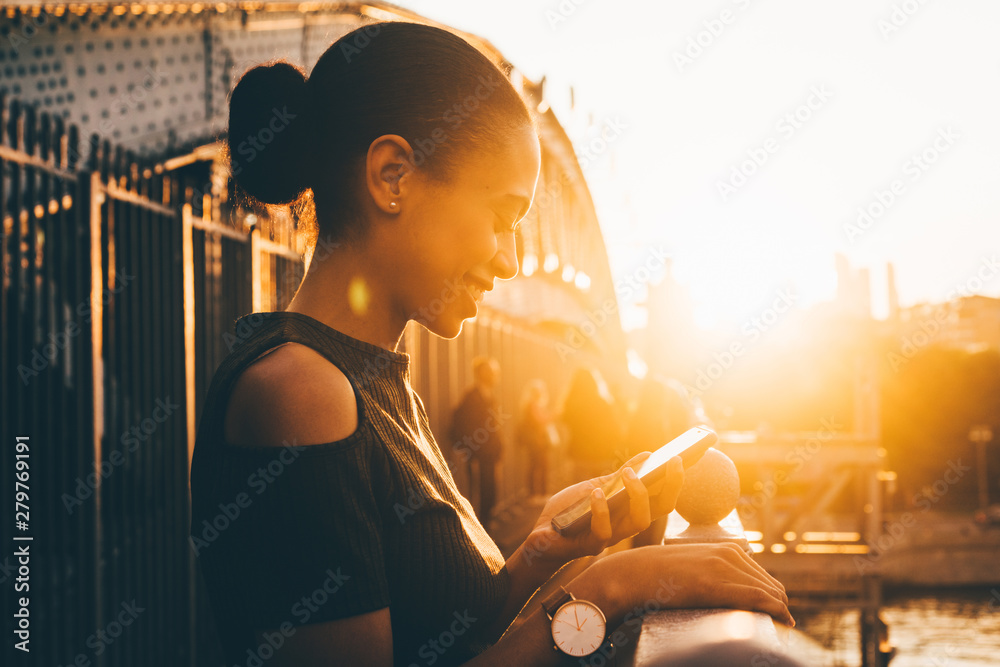 Fototapety, obrazy: An elegant young Brazilian female is using smartphone outdoors and smiling at the sunset.