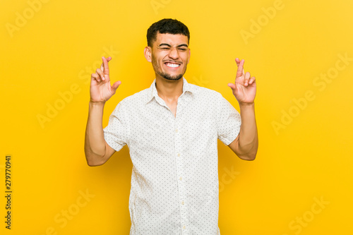 Photographie  Young hispanic man crossing fingers for having luck