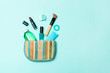 canvas print picture - Make up products spilling out of cosmetics bag on blue pastel background with empty space for your design