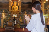 Religious Asian buddhist woman praying, chanting mantra to the lord Buddha with buddhist style rosary beads in hand