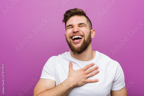 Fotografía  Young handsome caucasian man laughs out loudly keeping hand on chest