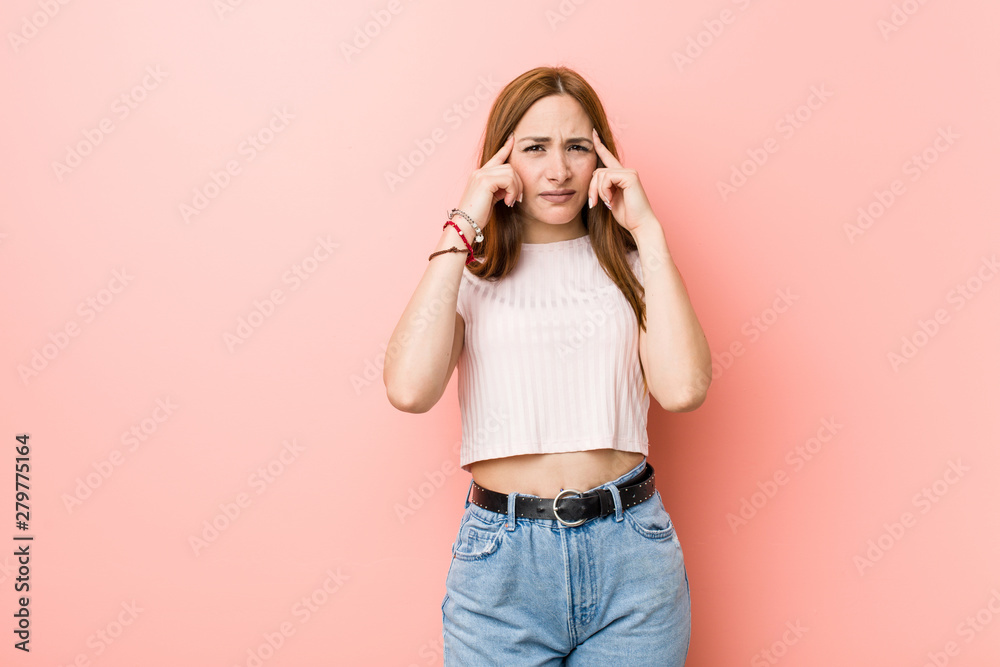 Fototapeta Young redhead ginger woman against a pink wall focused on a task, keeping forefingers pointing head.