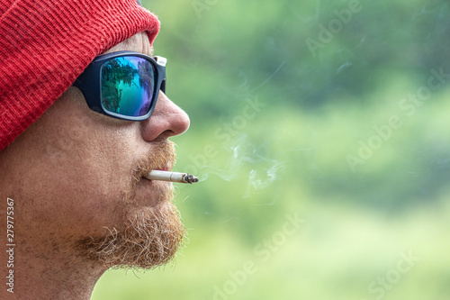 Canvastavla  brutal man in black sunglass smoking a cigarette in green forest, outdoor hipste