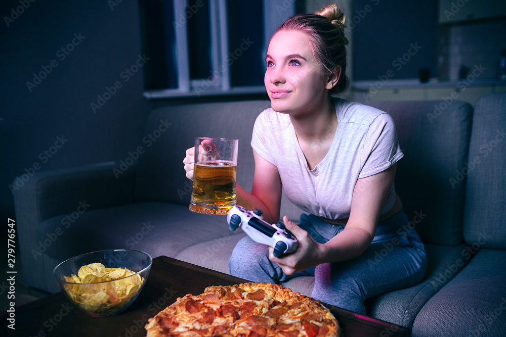 Fototapety, obrazy: Young woman playing game at night. Cheerful attractive model drink beer and look forward. Junk food on table. Enjoying game. Gamepad in hand.