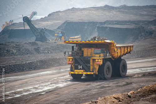 Fotografija Big yellow mining truck hauling rock in dusty coal mine