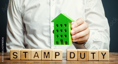 Foto Businessman and wooden blocks with the word Stamp duty and house