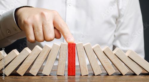 Fotografia Businessman stops collapse domino effect