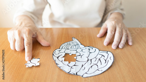 Photo Elderly woman hands putting missing white jigsaw puzzle piece down into the place as a human brain shape