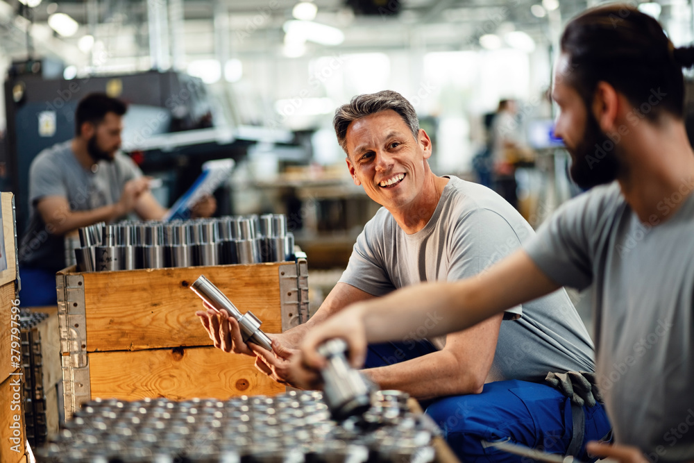 Fototapety, obrazy: Happy manual workers talking while working together at steel factory.