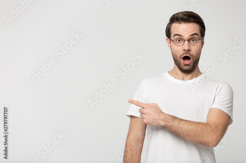 Surprised young man wearing glasses pointing finger aside at copyspace Canvas Print