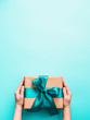 canvas print picture - Female hands hold big gift box on turquoise blue background, copy space. Caucasian girl hands holding gift box in craft wrapping paper with green satin ribbon. Christmas, New Year or Birthday present