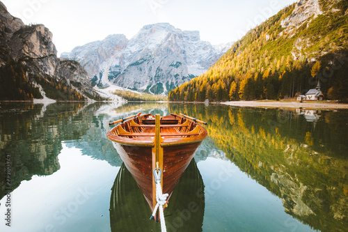 Foto auf Leinwand Wasserfalle Traditional rowing boat on a lake in the Alps in fall