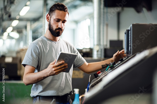 Fotografie, Obraz  Young worker operating a CNC machine while using digital tablet in industrial facility