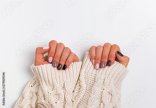 Woman;s hands in cozy knitted sweater shoing a manicure in pastel colors,