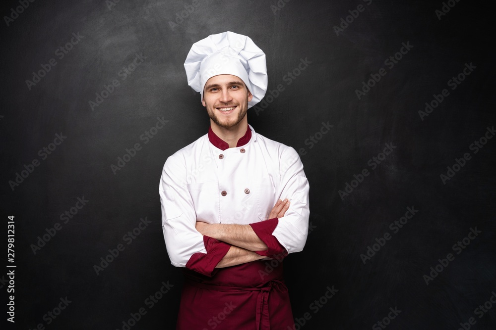 Fototapety, obrazy: Young male chef isolated on a black background.