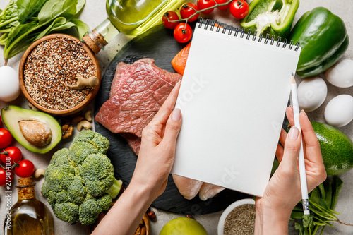 Fototapeta cropped view of woman holding empty notebook above food for ketogenic diet menu obraz