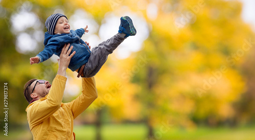 Obraz family, childhood and fatherhood concept - happy father and little son playing and having fun outdoors over autumn park background - fototapety do salonu