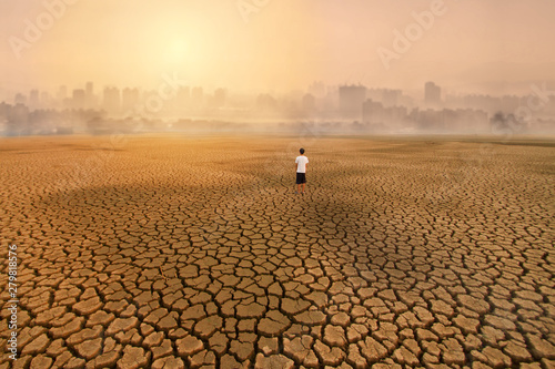 Fotografie, Obraz  a man standing at empty land of dry cracked earth and looking to the big city with air polluted environment metaphor Climate change, Water crisis, Environment pollution of activity from urban concept