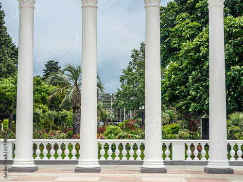 Billede på lærred White beautiful columns, part of the famous colonnades in Batumi, and green tropical trees behind of them