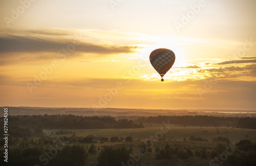 Poster Montgolfière / Dirigeable An air balloon flying over the field using heat technology - bright sunset