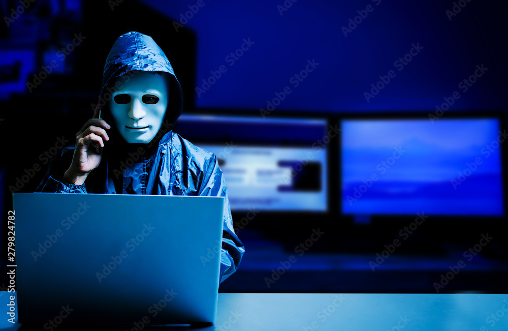Fototapeta Anonymous computer hacker in white mask and hoodie. Obscured dark face using laptop computer for cyber attack and calling on cellphone, Data thief, internet attack, darknet and cyber security concept.