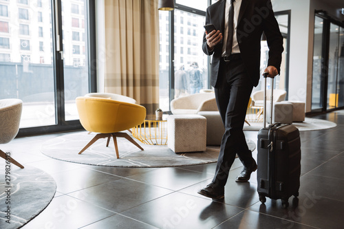 Fototapeta Cropped photo of successful businessman wearing suit holding smartphone and walking with suitcase in hotel lobby obraz