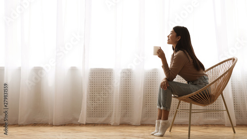 Carta da parati Girl Sitting in Armchair And Enjoying Coffee