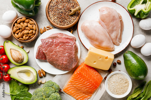top view of raw salmon, chicken breasts and meat on white plates near nuts, eggs and vegetables, ketogenic diet menu