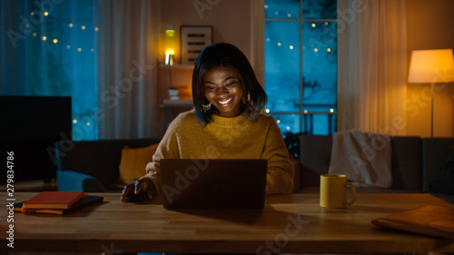 Photo Portrait of Beautiful Smiling Black Girl Working on a Laptop while Sitting at Her Desk at Home