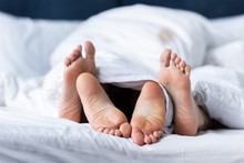 Partial View Of Two Barefoot Lesbians Lying Under Blanket