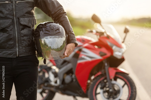 Obraz na płótnie Handsome motorcyclist wear leather jacket and holding helmet on the road