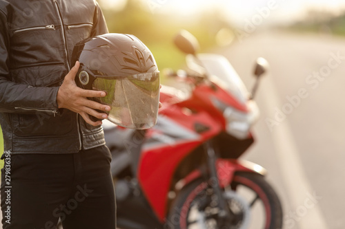 Fotografía  Handsome motorcyclist wear leather jacket and holding helmet on the road